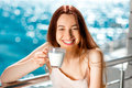 Young and pretty woman on the balcony smiling drinking milk blue water background Royalty Free Stock Image