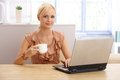Young pretty woman with coffee and laptop drinking holding cup using computer smiling at camera Stock Photo