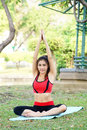 Young pretty woman doing yoga exercises in park the Royalty Free Stock Image