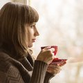 Young Pretty Woman Drinking Coffee  near Window in Cafe Royalty Free Stock Photo