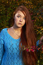 A young pretty woman and golden autumn with big blue eyes orange hair wearing blue sweater looks straight in front of her there is Royalty Free Stock Photo
