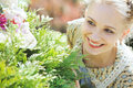 Young pretty woman hiding behind a green bush Stock Image