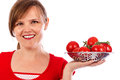 Young pretty woman holding a bowl of ripe tomatoes against white background Royalty Free Stock Image