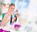 Young pretty woman holding weights and doing body training indoor Royalty Free Stock Images