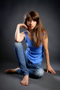 Young pretty woman in jeans  smiling and sitting on the floor Royalty Free Stock Image