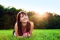 Young pretty woman lying on the grass and smiling at summer sunset Royalty Free Stock Photo