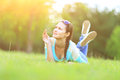 Young pretty woman lying on grass at summer sunset. Natural happiness, fun and harmony. Royalty Free Stock Photo