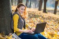 Young pretty woman in the park with laptop Royalty Free Stock Photo