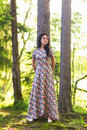 Young pretty woman poses showing dress summer outdoors in sunset