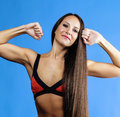 Young pretty woman posing in bikini on blue real background studio shot hot sporty brunette Stock Photo