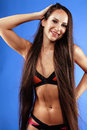 Young pretty woman posing in bikini on blue real background studio shot hot sporty brunette Royalty Free Stock Photos