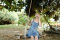 Young pretty woman riding swing and speaking by smatrphone, sand and tree in background. Royalty Free Stock Photo