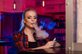 Young pretty woman in a shirt in a cage smoke an electronic cigarette at the vape bar Royalty Free Stock Photo
