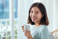 Young pretty woman sitting at opened window drinking coffee Royalty Free Stock Photo
