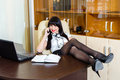 Young pretty woman speaks by phone in office