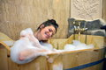Young pretty woman taking a bubble bath smiling Stock Photography