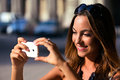 Young and pretty woman taking photo with her smartphone while sightseeing Royalty Free Stock Image