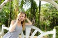 Young pretty woman talking by smartphone with palms in background, sitting on swing. Royalty Free Stock Photo