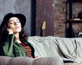 Young pretty woman waiting alone in modern loft studio, hipster in hat, fashion musician concept, lifestyle people Royalty Free Stock Photo
