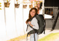 Young pretty woman wearing casual clothing and backpack standing in front of camera smiling happily, backpacker concept
