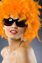 Young pretty woman wearing an orange feather wig Stock Images