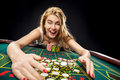 Young pretty women playing roulette wins at the casino Royalty Free Stock Photo