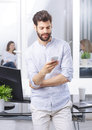 Young professional with handy portrait of standing at office while using his mobile creative manager checking emails on his Royalty Free Stock Photos
