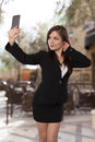 Young professional looking woman takes a self portrait with her beautiful business selfie cell phone Royalty Free Stock Image