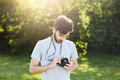 Young professional photographer looking at his camera trying to tune objective going to make photos of nature landscapes. Handsome Royalty Free Stock Photo