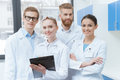 stock image of  Young professional scientists in lab coats smiling at camera