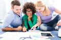 Young professionals sitting on floor discussing papers group of creative working smiling Royalty Free Stock Image