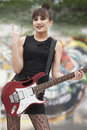 Young punk rock girl giving devil horns with her hand and holding guitar Stock Photos