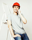 Young real hard worker man isolated on white background on ladder smiling posing, business people concept