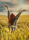 Young red hair woman standing back hands up to breathtaking view fashion on of dramatic storm sky in the field Stock Images