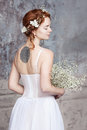 Young red-haired bride in elegant wedding dress. She stands with her back to the viewer. Her eyes are dreamy closed. Royalty Free Stock Photo