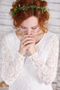 Young red haired bride in a green wreath gently smiling her hands folded prayer Stock Photo