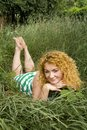 Young red-haired girl lying in the grass Stock Image