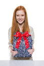 Young red haired girl presenting a gift well dressed presents present with big smile Royalty Free Stock Photos