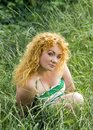 Young red-haired girl sits in the grass Royalty Free Stock Photo