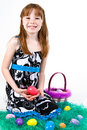 Young red headed female child holding easter eggs front her sitting fake grass more easter eggs basket Royalty Free Stock Images