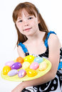 Young red headed female child holding plate easter eggs front her Royalty Free Stock Images