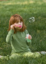 Young red headed girl blowing bubbles shade tree early spring morning Royalty Free Stock Photography