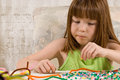 Young red headed girl confused look her face making bead bracelets using pipe cleaners numerous colorful plastic beads Royalty Free Stock Photo