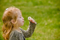 Young red headed girl leopard print attempts to blow dandelion seeds weed has picked field green grass Royalty Free Stock Photography
