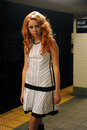 Young redhead fashion model posing in nyc subway dressed designer s clothes Royalty Free Stock Photography