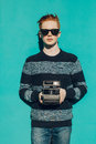 Young redhead man in a sweater and jeans and sunglasses standing next to turquoise wall and taking photos vintage camera warm summ Royalty Free Stock Photography