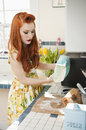 Young redheaded woman in preparation for baking Royalty Free Stock Images