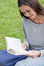 Young relaxed girl sitting in a public garden while reading a bo Royalty Free Stock Image