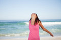 Young relaxed woman standing on the beach with her arms spread Royalty Free Stock Photo