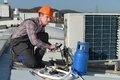 Young repairman on the roof fixing air conditioning system model is actual electrician Stock Image